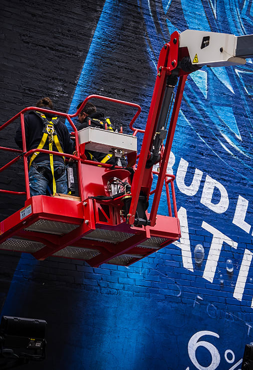 2 artists on a platform crane painting a bud light platinum mural on the side of a building in st. louis