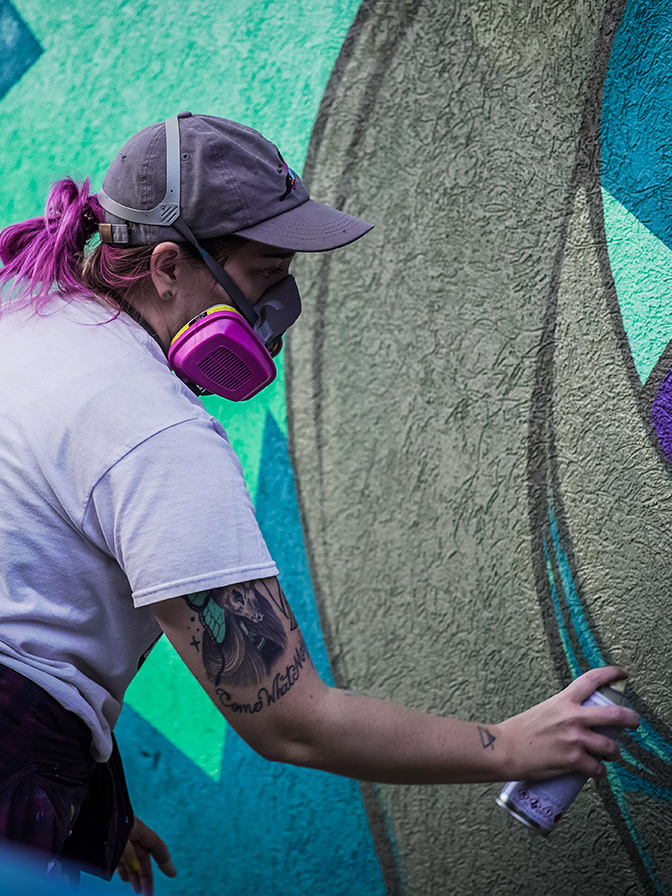 close up of a woman wearing a pink mask while spray painting an outdoor mural on a building