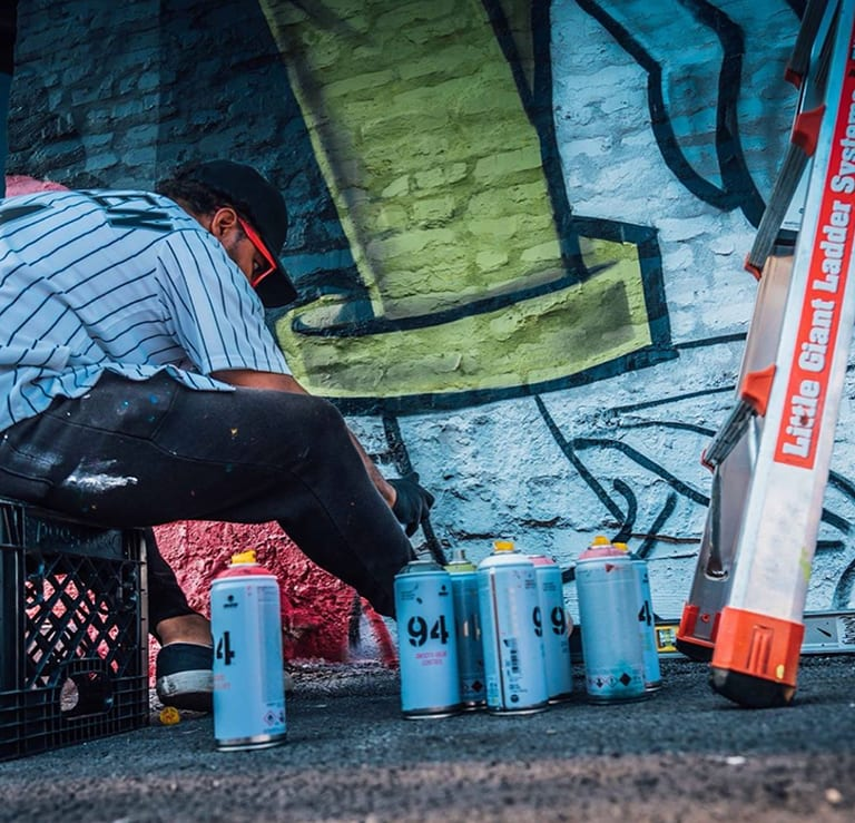 artist sitting on crate next to several empty spray paint canisters while working on an outdoor mural