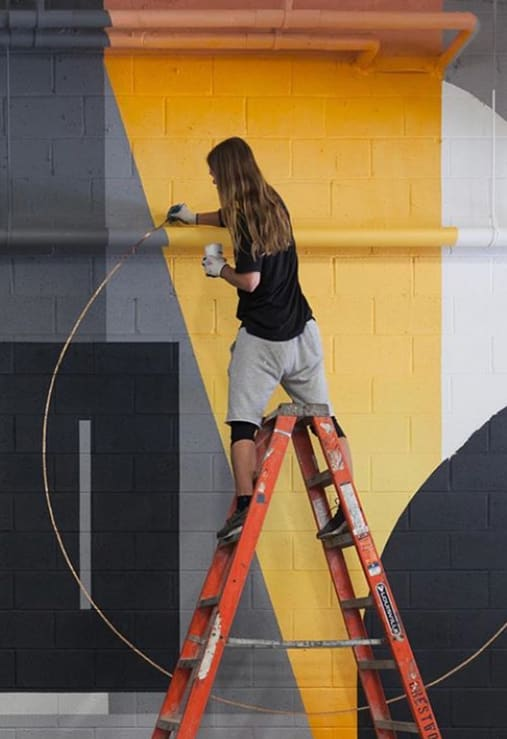 artist straddling the top of a ladder while painting a mural in a restaurant