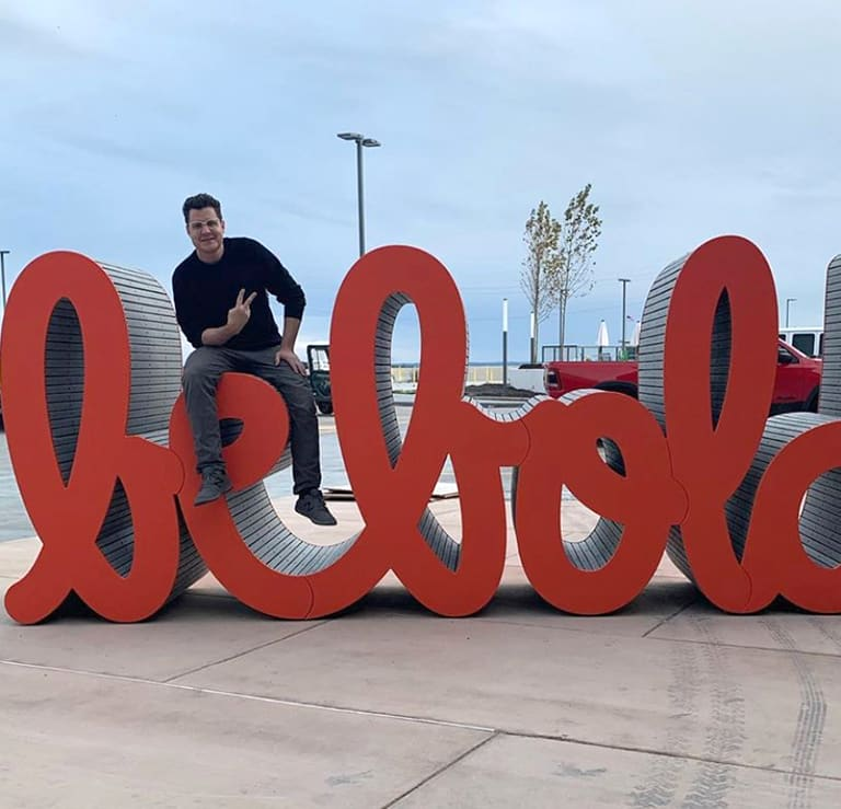 artist sitting on a sculpture that spells the words Be Bold