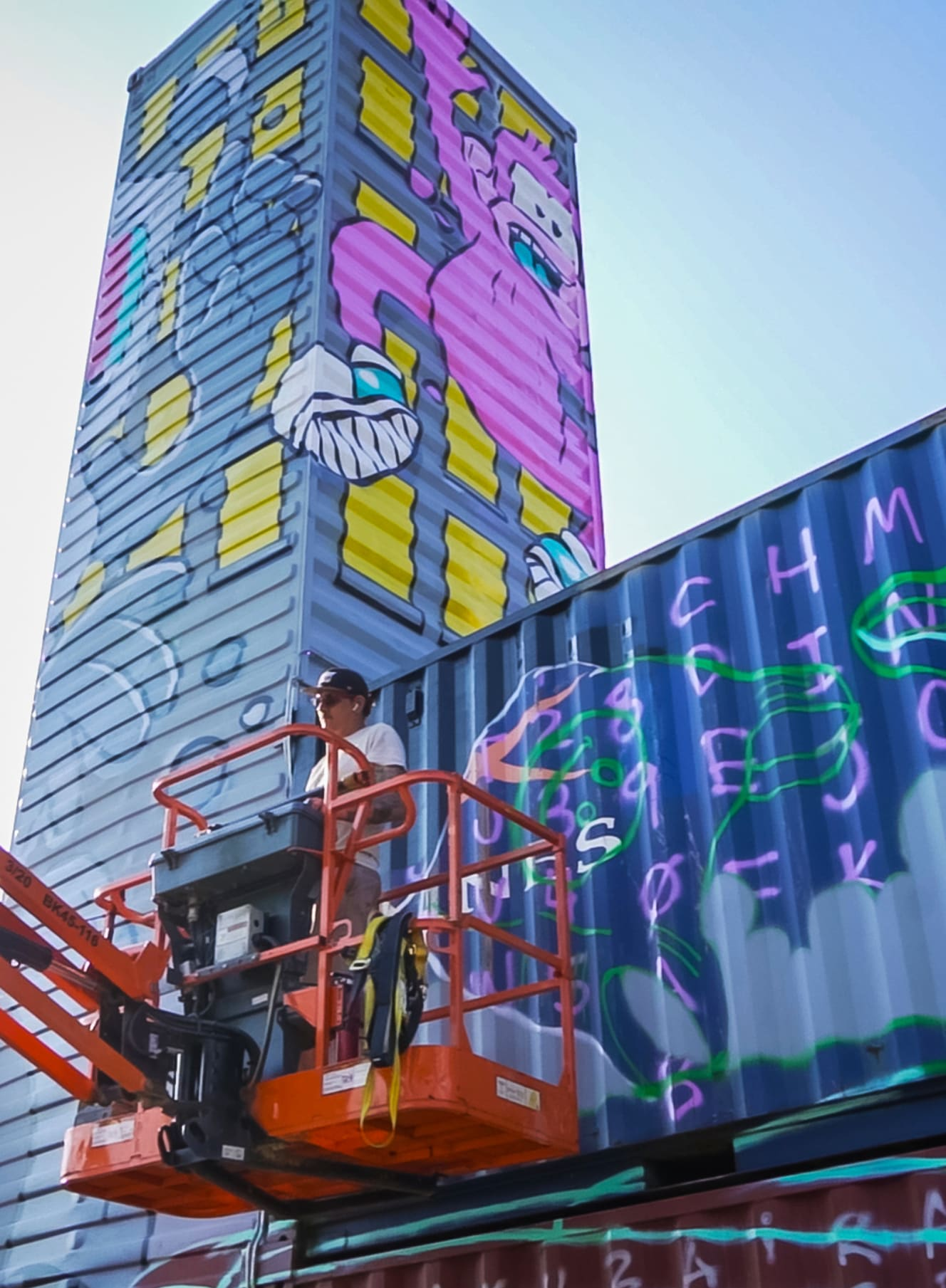 mural artist on a crane platform painting tall shipping containers