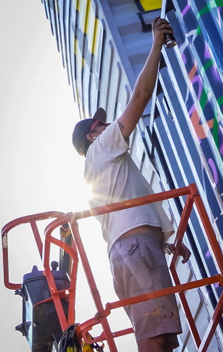 close up of artist standing on a crane platform painting a mural on a shipping container