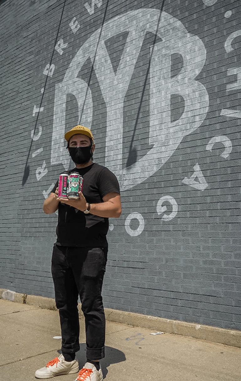 Black Jones standing with the beer cans he designed for Murals for medical relief
