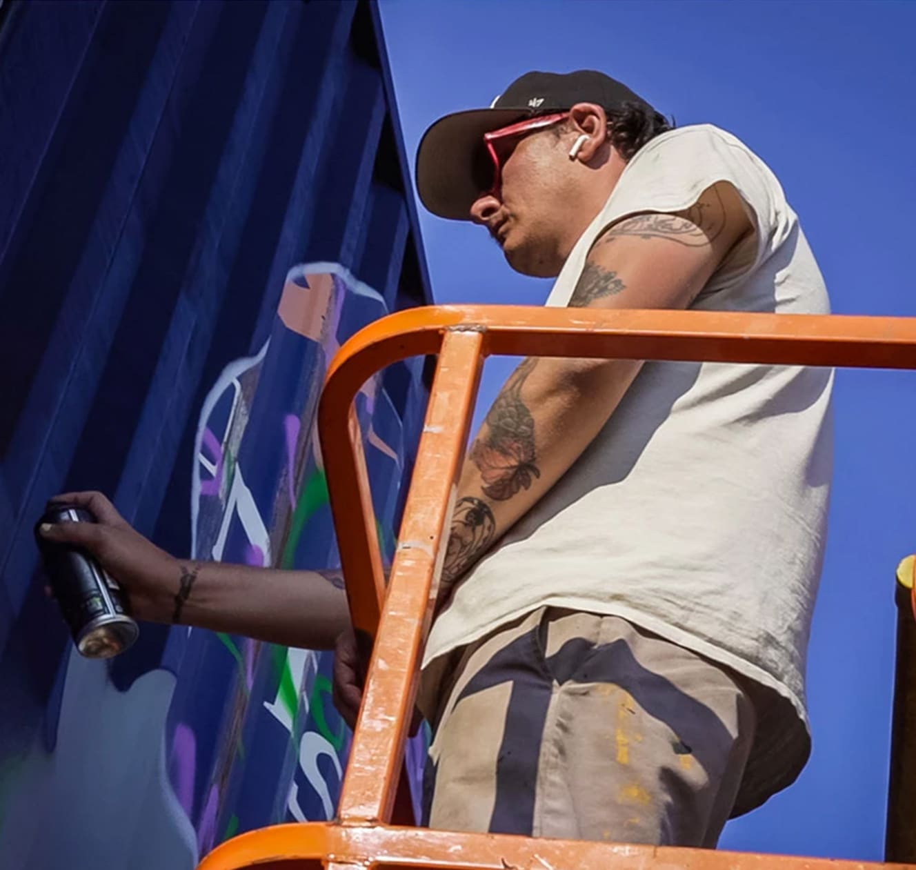 close up of mural artist spray painting a shipping container