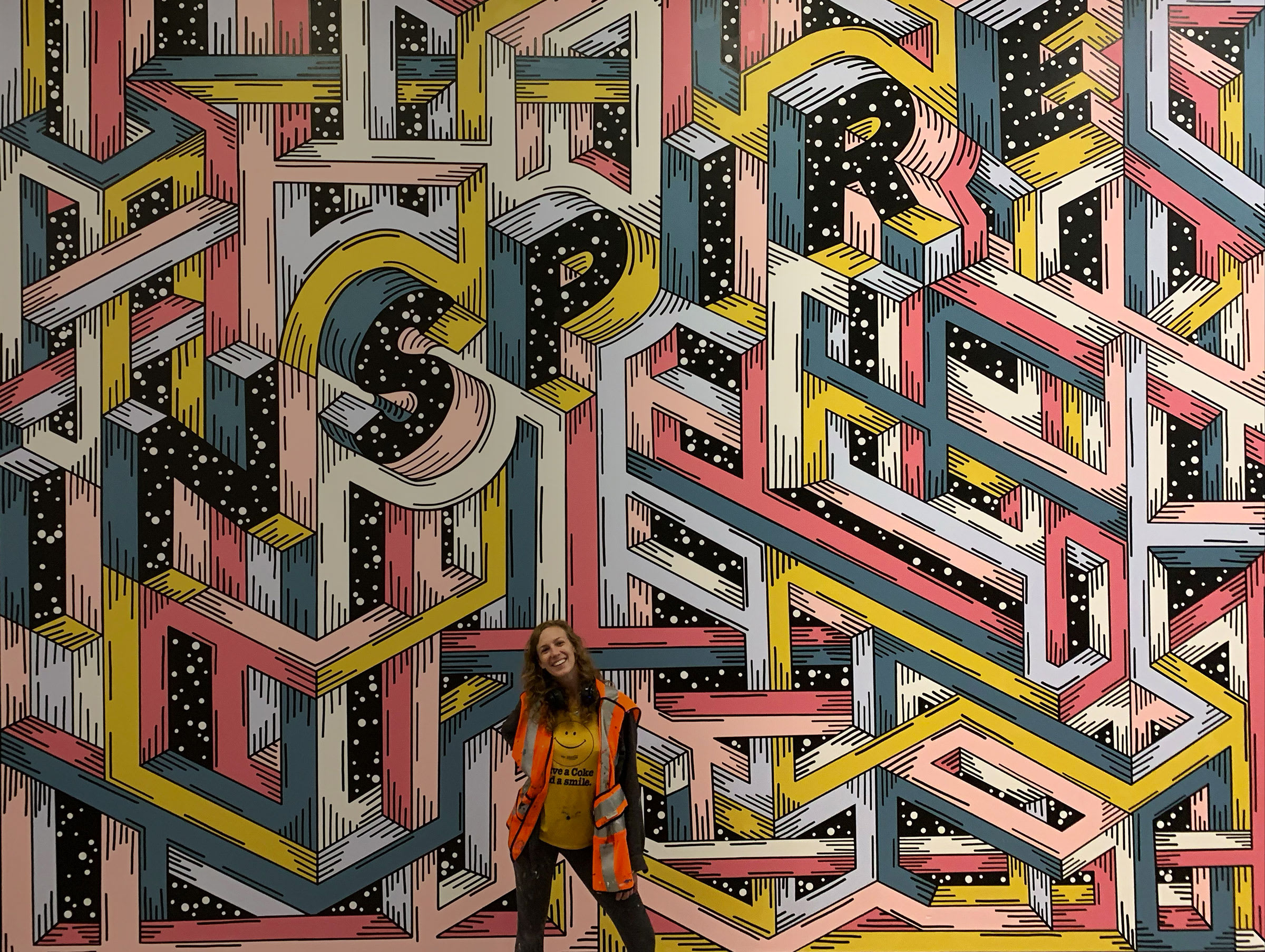 artist standing in front of her mural marketing campaign for Brookfield Properties that is a maze design with the word Inspire worked in