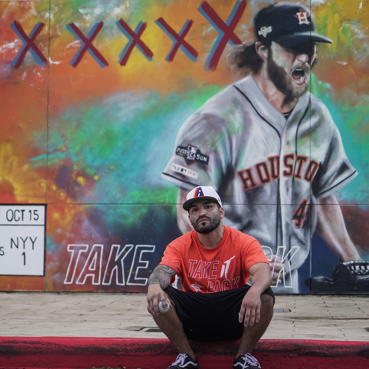 artist sitting in front of Houston Astros mural of Garrett Cole