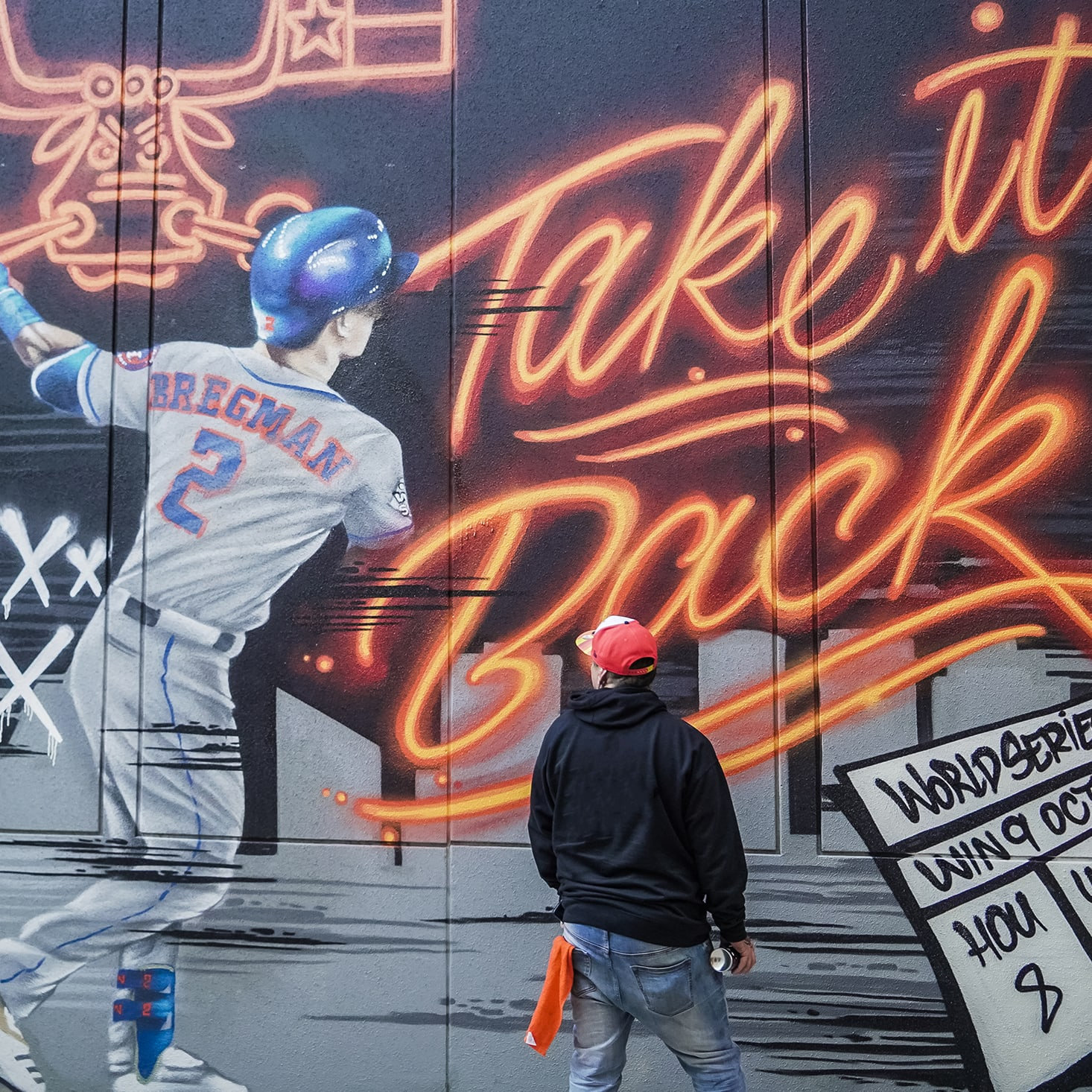 artist standing in front of baseball wall mural