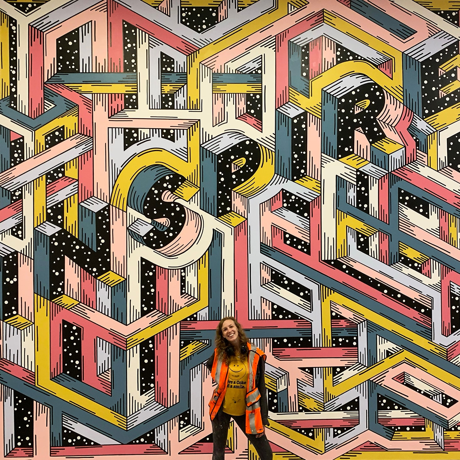 artist standing in front of colorful inspire mural