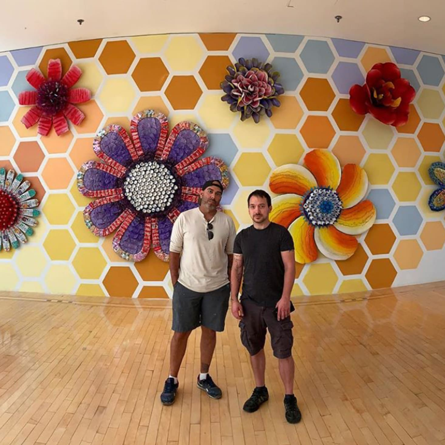 two artists standing in front of recycled material mural