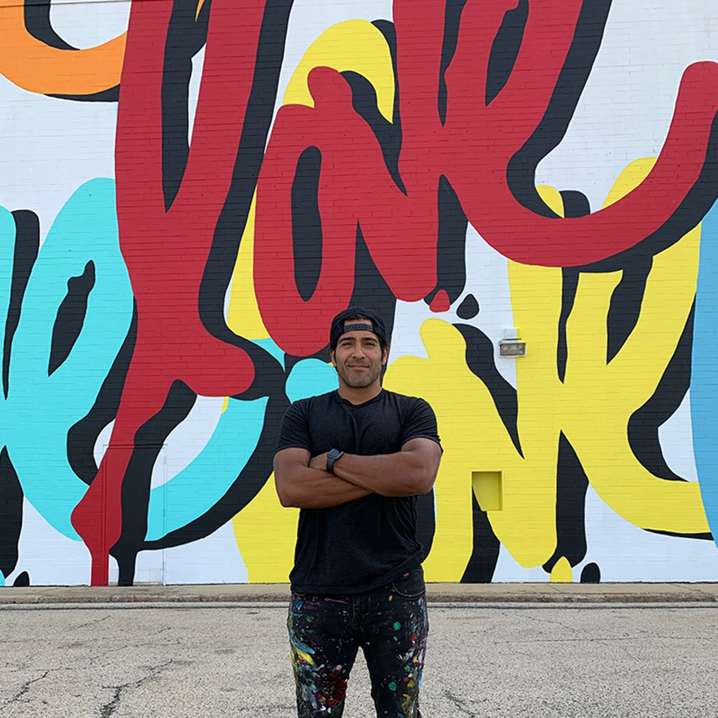 artist standing in front of painted 'love' mural on side of building