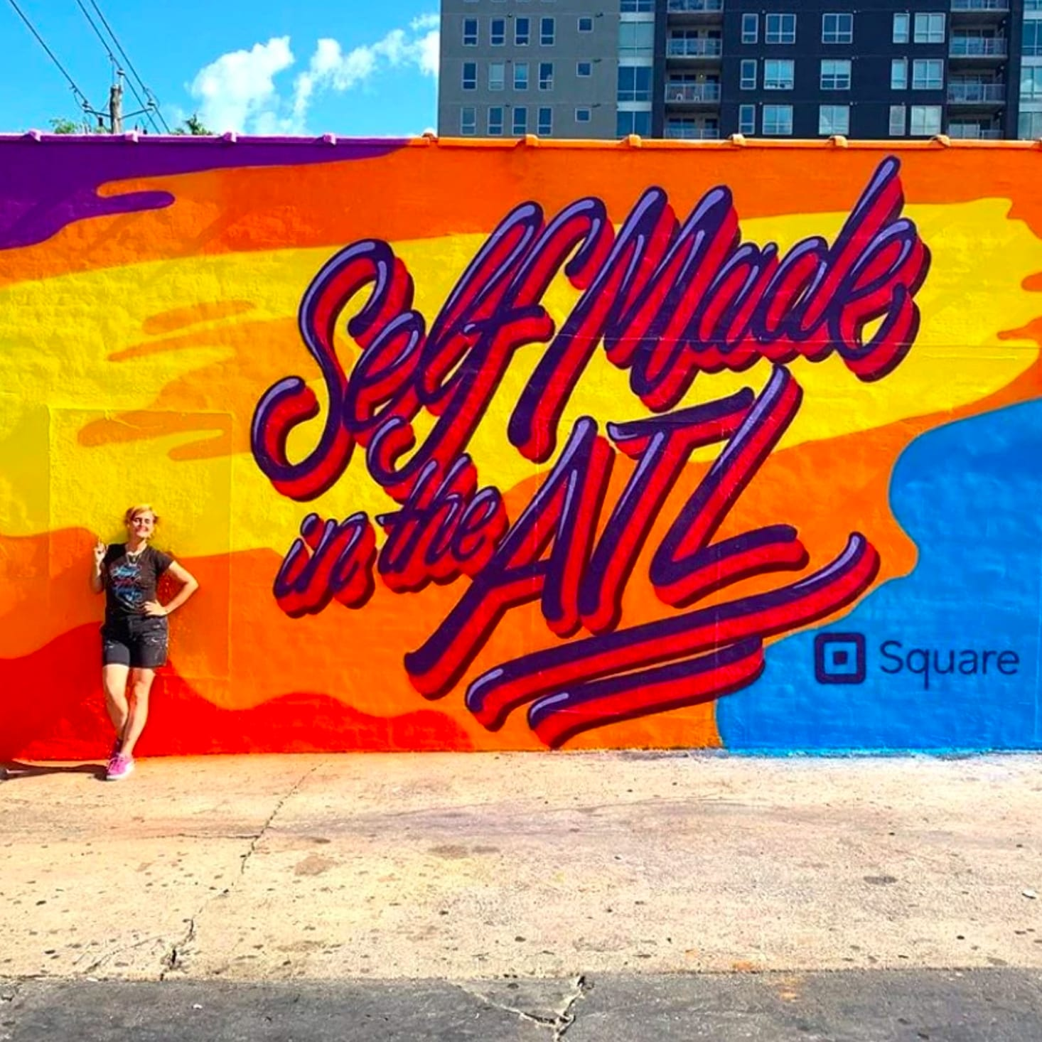 artist standing in front of painted exterior wall mural in atlanta