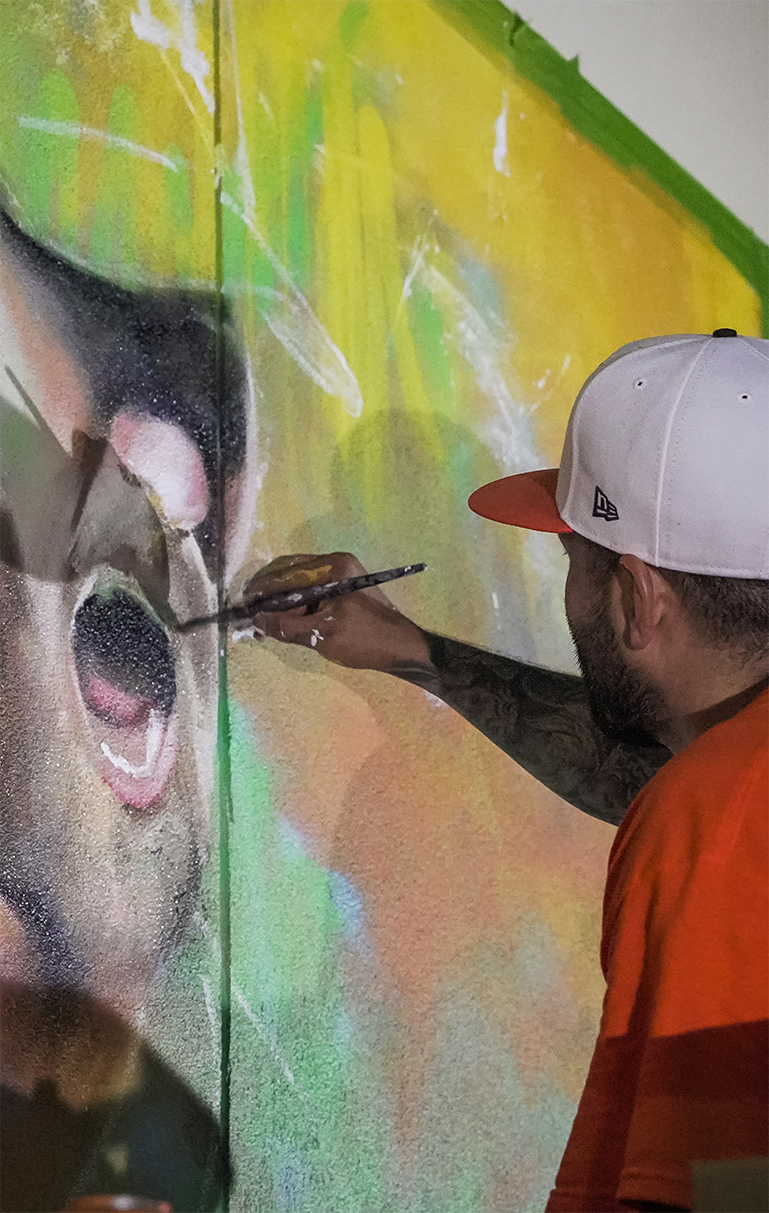 close up of mural artist painting a baseball player from the houston astros