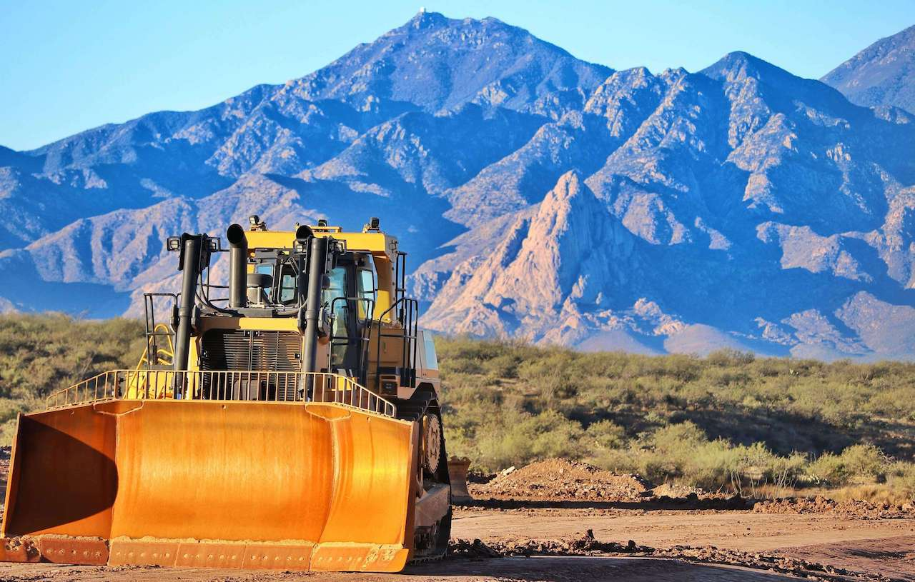 Large Cat Bulldozer By Mountains In Daylight