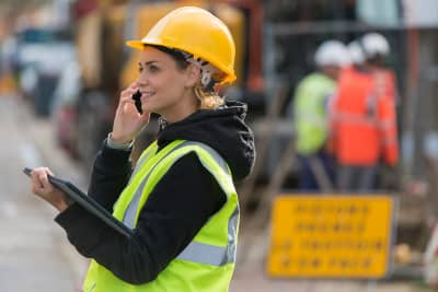 Woman Construction Worker On Phone Wearing Personal Protective Equipment