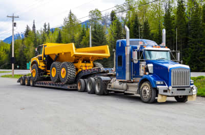 Yellow Articulated Dump Truck Or Rock Truck Being Transported On Flatbed Trailer