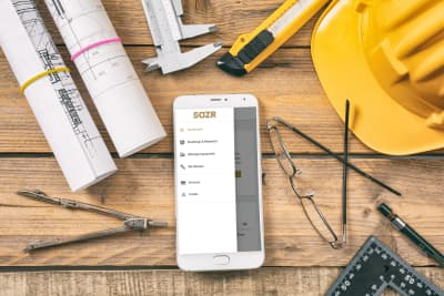 Cellphone With DOZR Dashboard On Display On Workbench Surrounded By Construction Tools