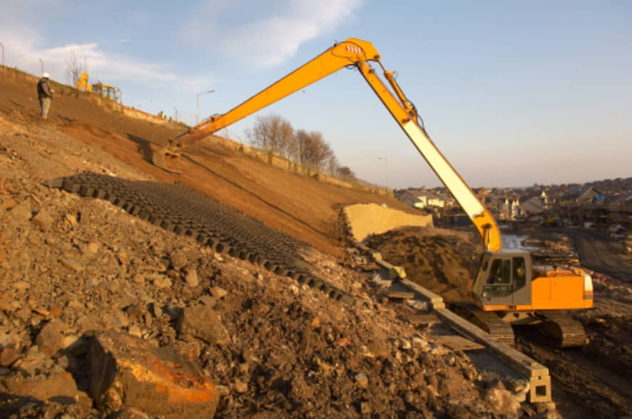 Long reach excavator digging on hill