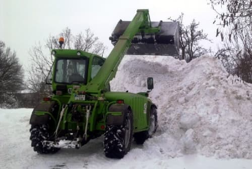 Telehandler shoveling snow big pile
