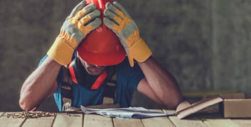 construction worker holding head with hands