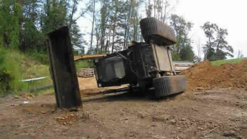 A skid steer rolled over on its side