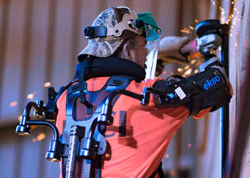 construction worker welding while wearing exoskeleton