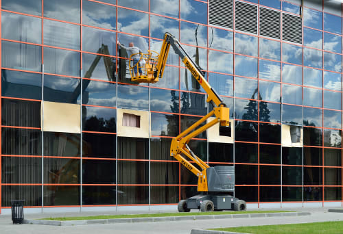 Articulating boom lift being used to clean windows