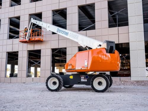 A snorkel straight boom lift with construction worker on construction site