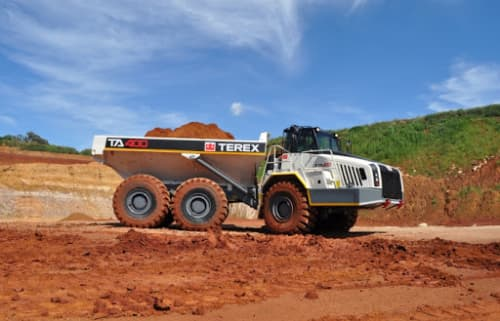 A Terex articulating dump truck driving over dirt on the construction site