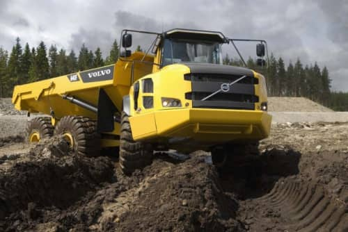 volvo construction rock truck driving over piles of dirt