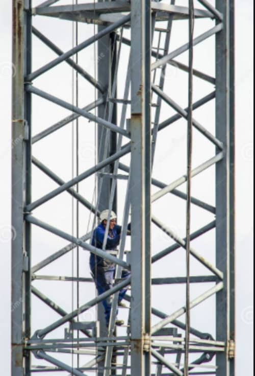 person climbing up the cage of a tower crane
