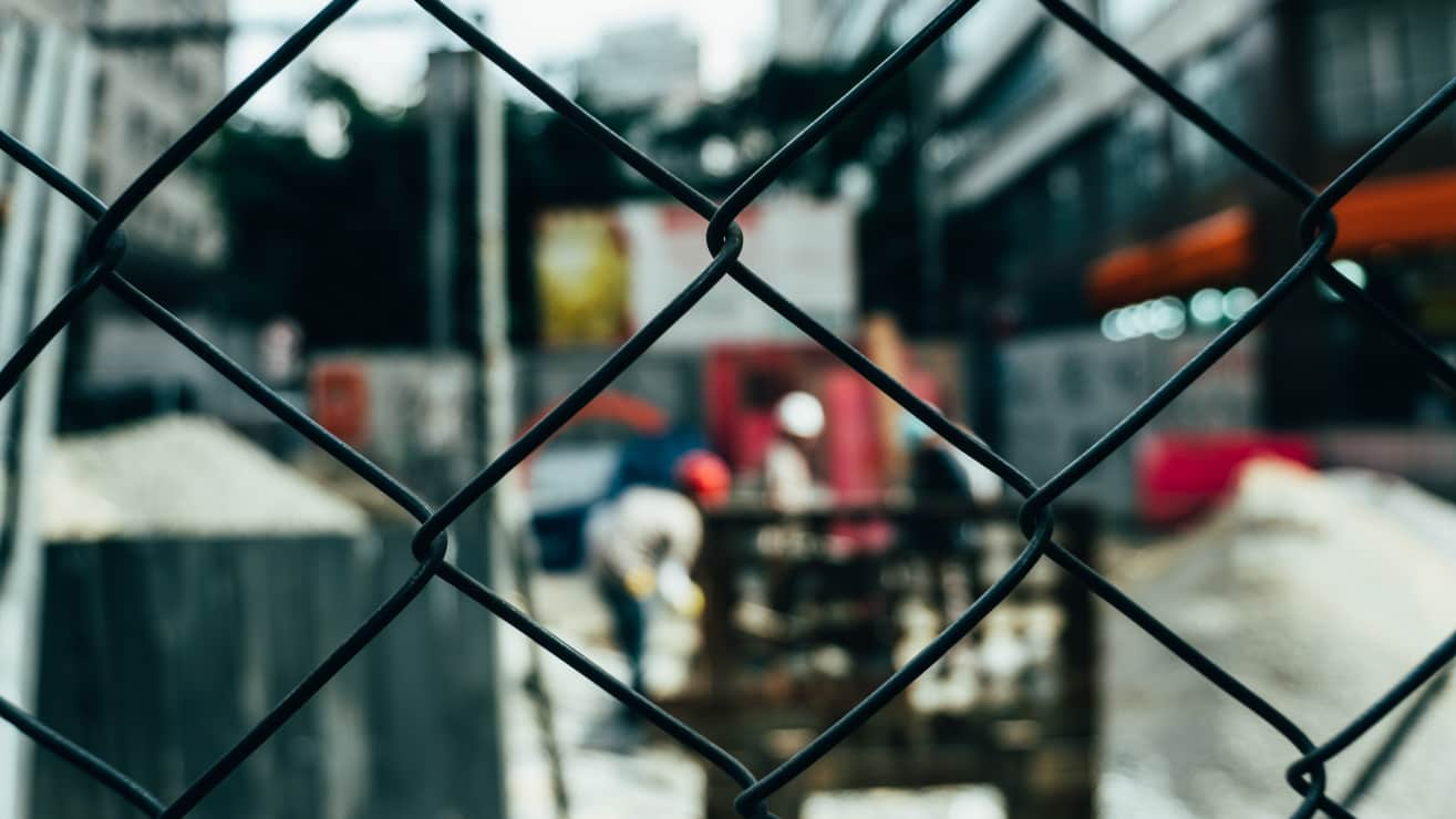 Closeup Of Fence With Construction In Background