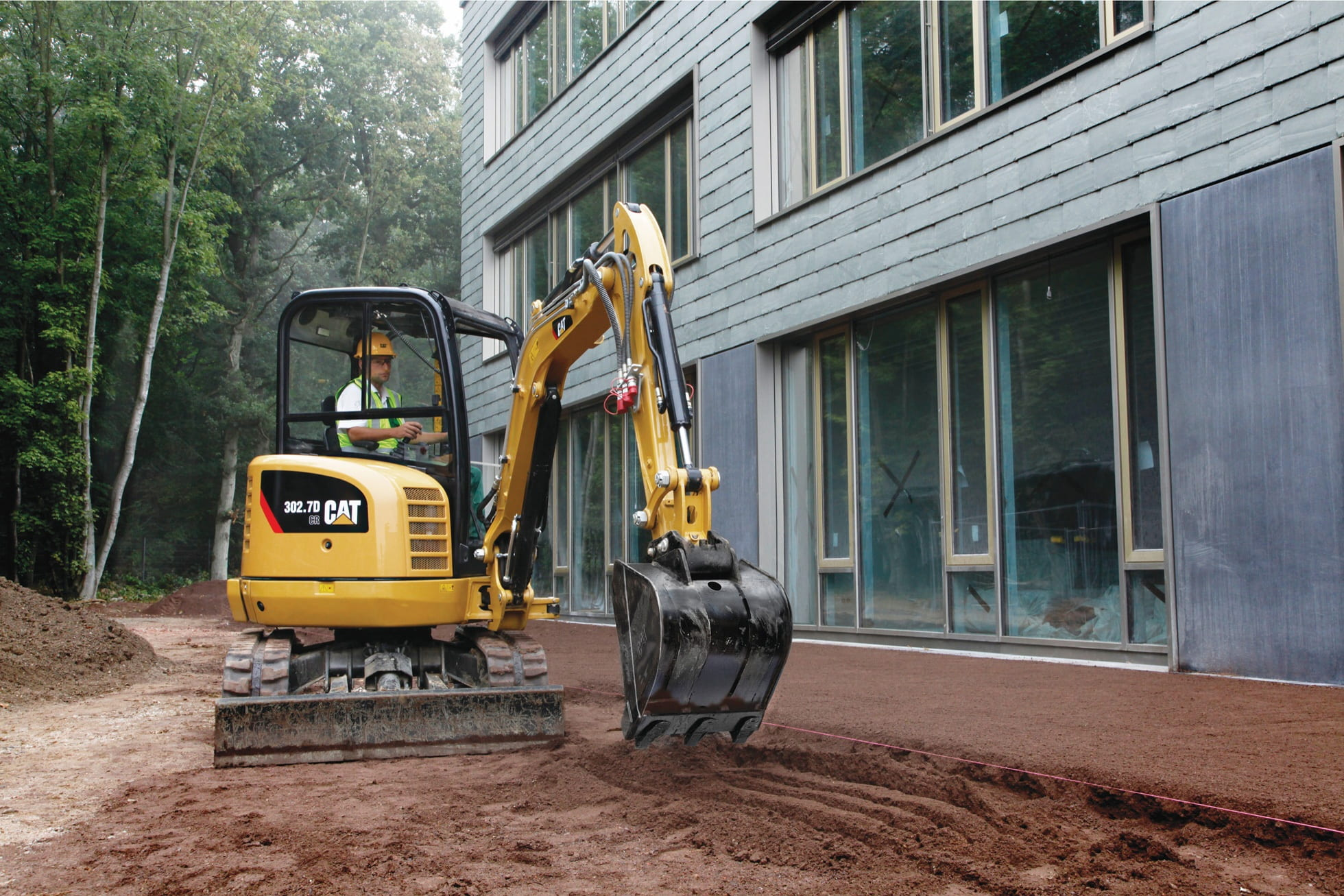 A mini ex digging behind a building project