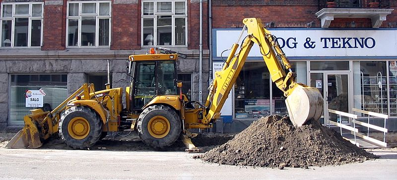 A backhoe parked and digging with hoe