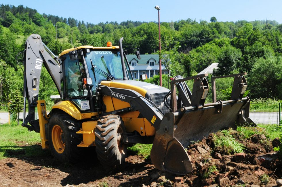 Volvo backhoe digging up grass with a bucket