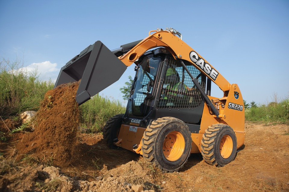CASE skid steer with a bucket attachment dumping dirt