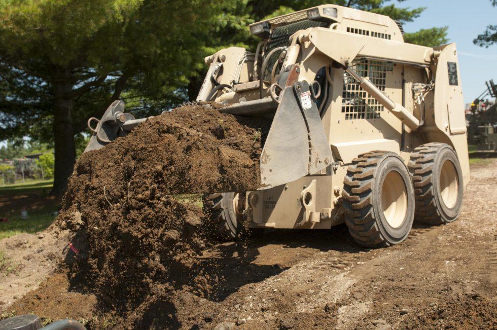 Skid steer dumping a load of dirt
