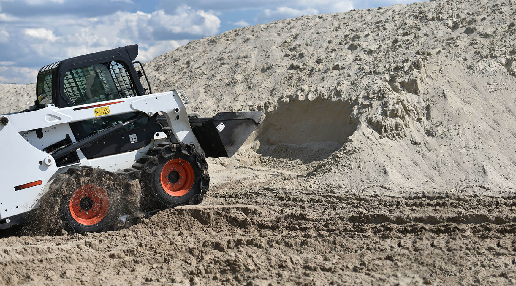 Wheeled Skid Steer Digging in Dirt in Ontario