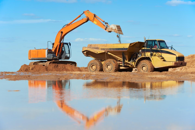 excavator dumping dirt into rock truck