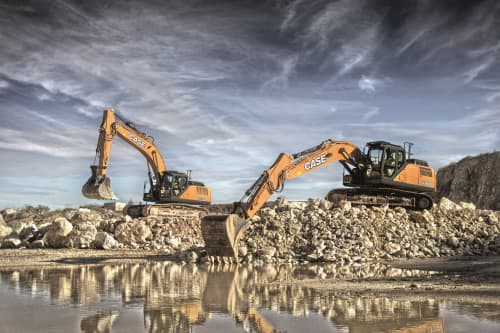2 yellow excavators on a rock pile near a body of water.