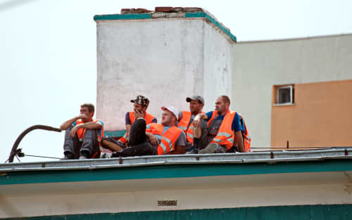 Workers sitting on a roof