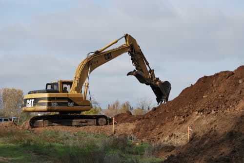 A yellow excavator digging from a dirt pile.
