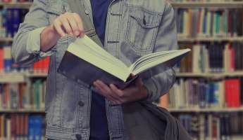Student holding book in a University Library