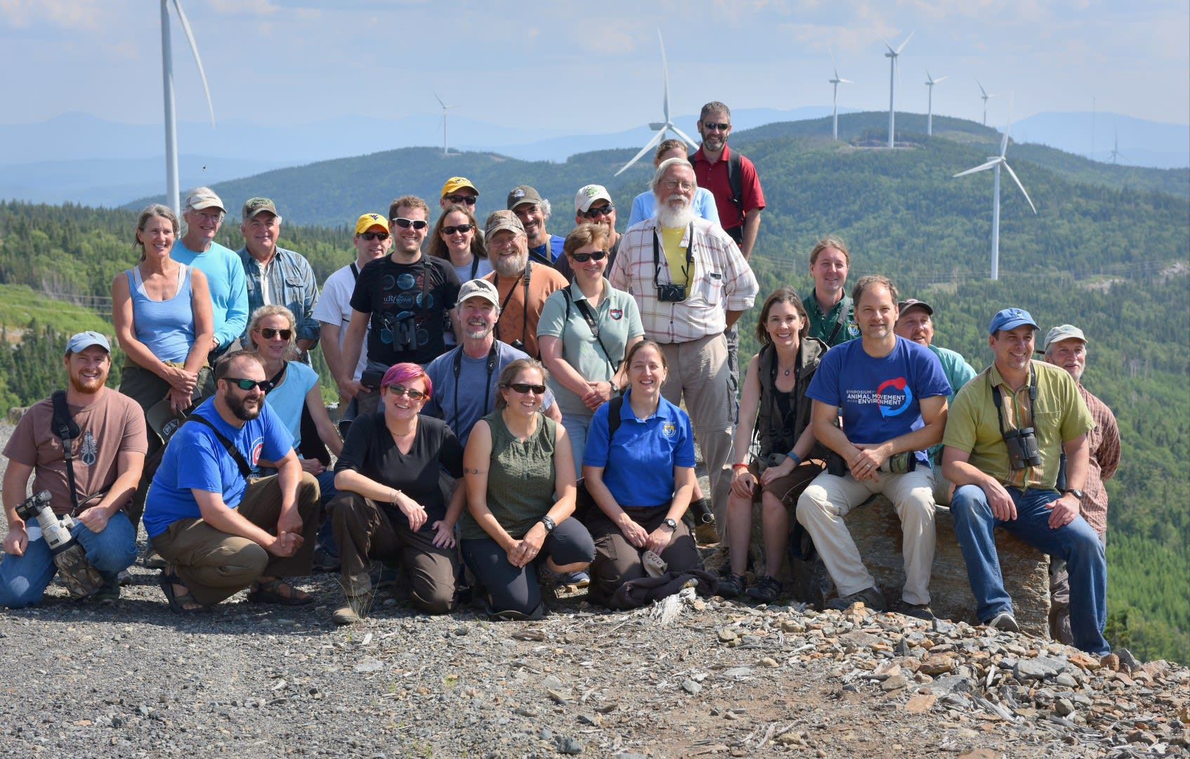 The group is shown during a field trip to a wind farm. Peg standing far left. Tom kneeling center second row. Dr. Todd Katzner stands above all others in the red shirt. Photo by Craig Koppie.