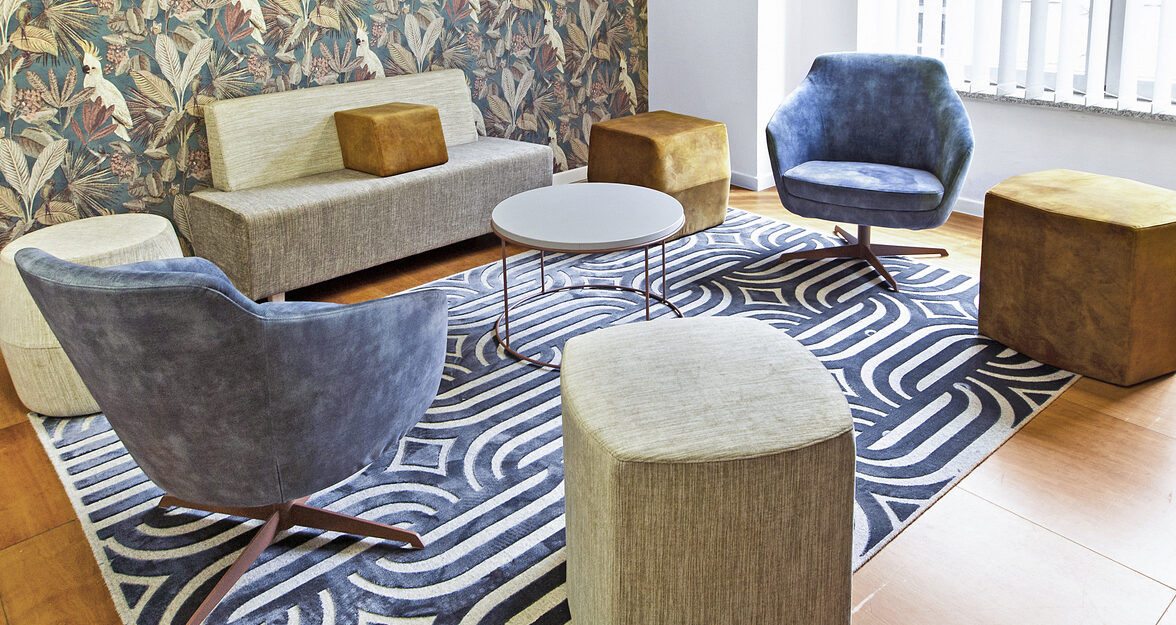 Lounge with lounge chairs, table, carpet, bench and wallpaper