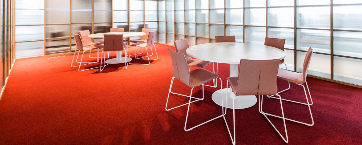 Vergaderzaal met witte stoelen en rood tapijt