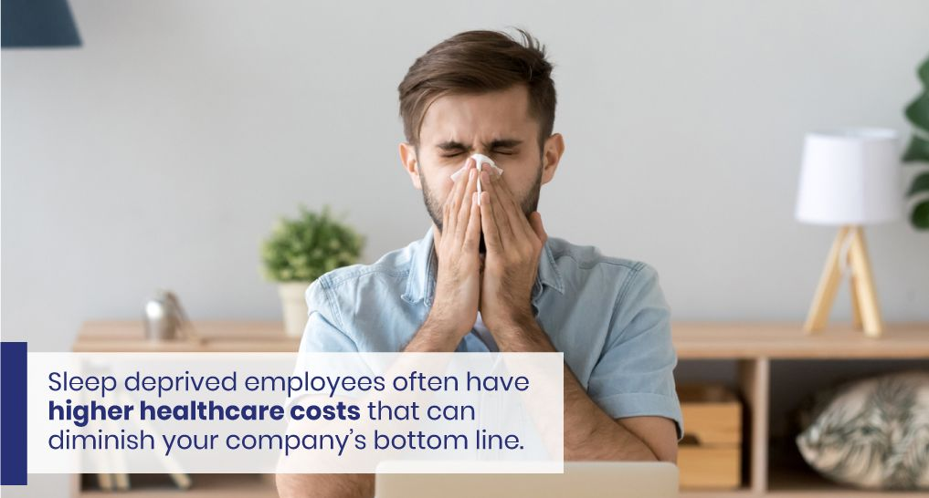 An Employee working at their desk blowing their nose because they're sick