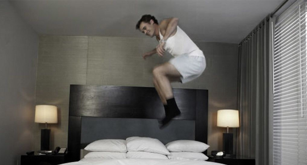 Man jumping on a bed