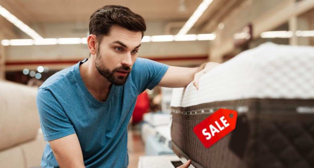 Man looking at mattress with tag that says it's on sale