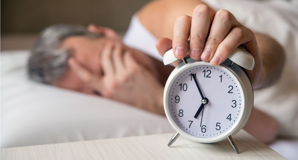 Man holding an alarm clock like he doesn't want to wake up